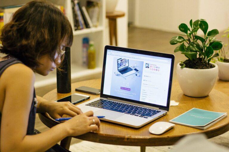 Foto de uma moça de blusa preta em uma mesa de madeira com um computador em cima. Ao lado vemos um caderno e um vaso de planta. Ao fundo vemos uma sala com uma estante branca. Imagem ilustrativa para texto franquias 2021 tendências.