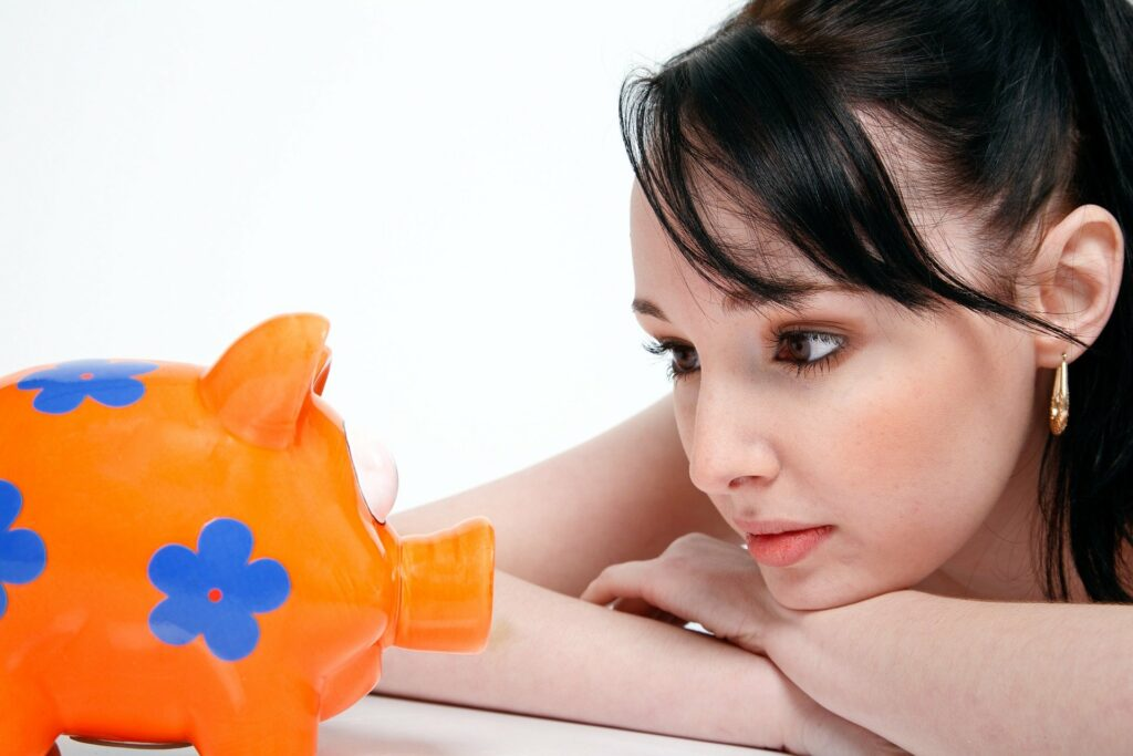 Foto de uma mulher olhando para um cofrinho em formato de porco, laranja e azul (imagem ilustrativa). Texto: pequenos negócios lucrativos.