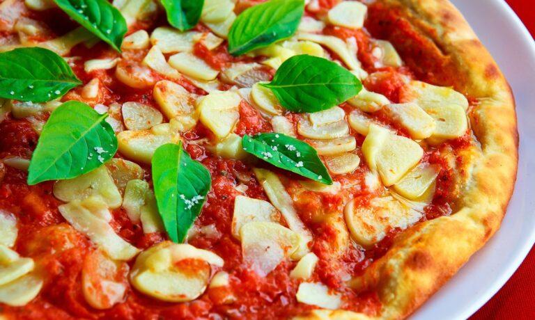 Imagem de uma pizza com muito molho, folhas e queijos. Imagem ilustrativa para texto franquia pizza hut.