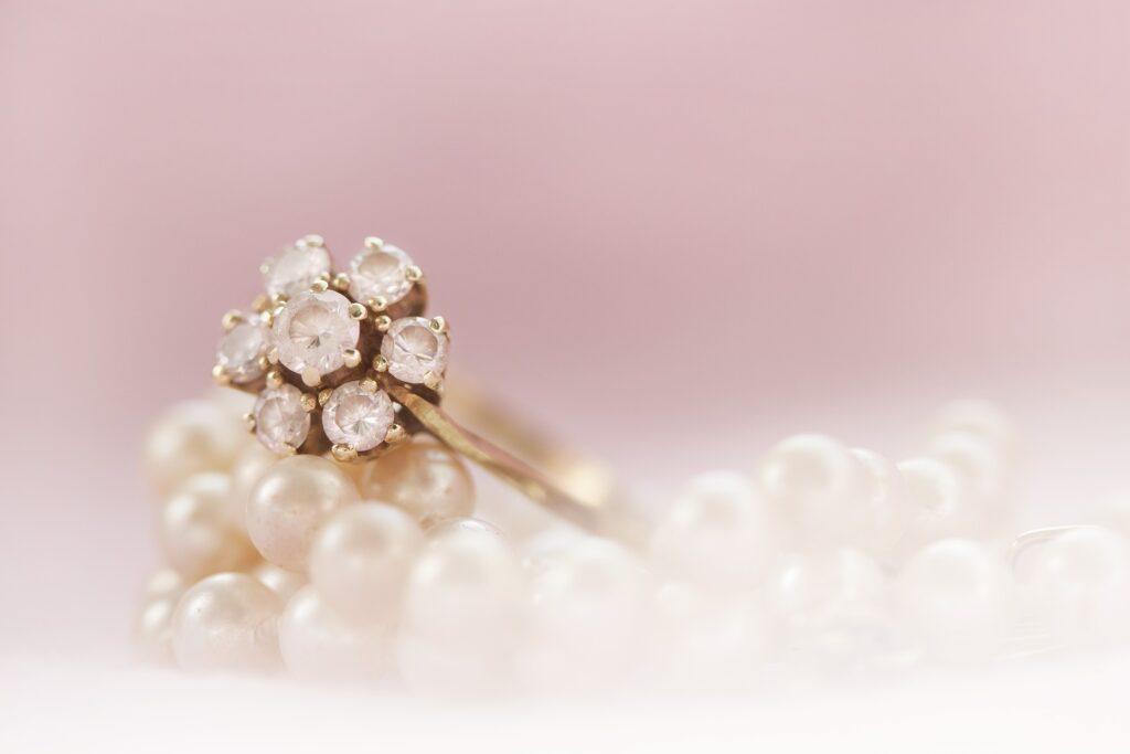 Foto de um anel com pedras, em cima de algumas pérolas. Temos um fundo rosa claro (imagem ilustrativa). Texto: pequenos negócios lucrativos.