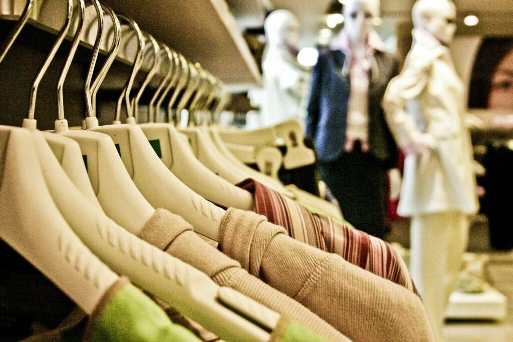 Foto de uma arara com roupas em uma loja. Vemos parte de blusas bege, vermelha e verde. Ao fundo vemos três manequins brancos com roupas pretas e brancas, além de mais araras (imagem ilustrativa). Texto: franquia hering.
