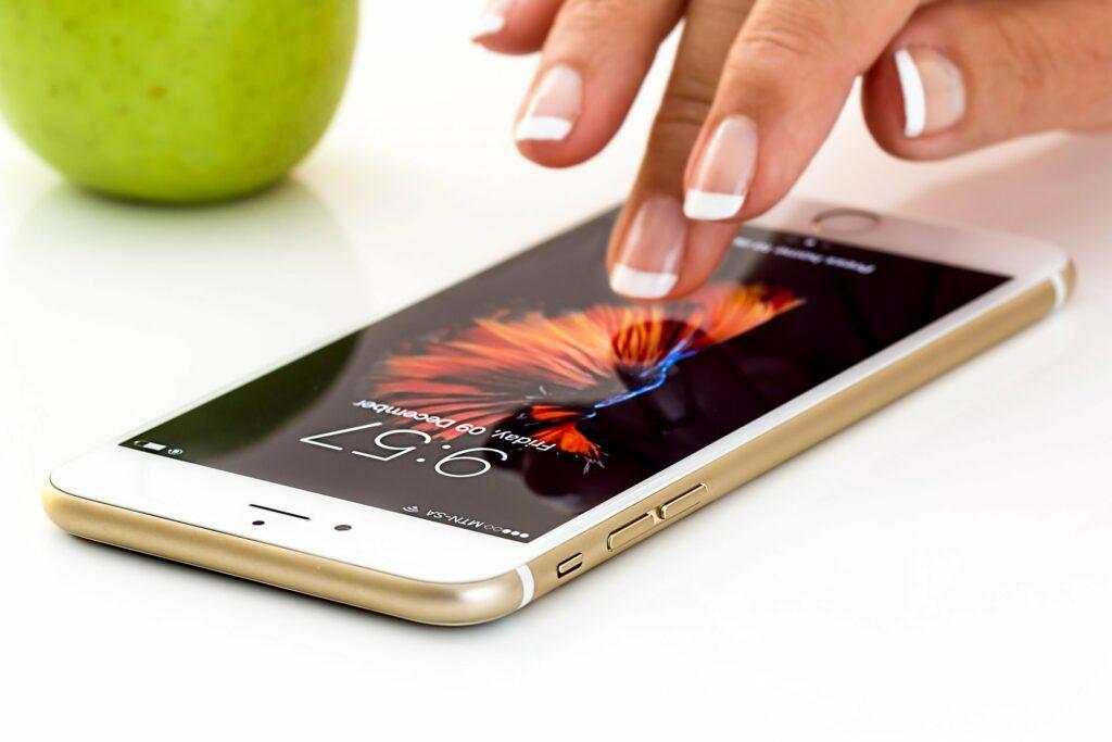 Mão de uma pessoa tocando em um celular numa mesa branca, ao lado vemos uma maça verde.
