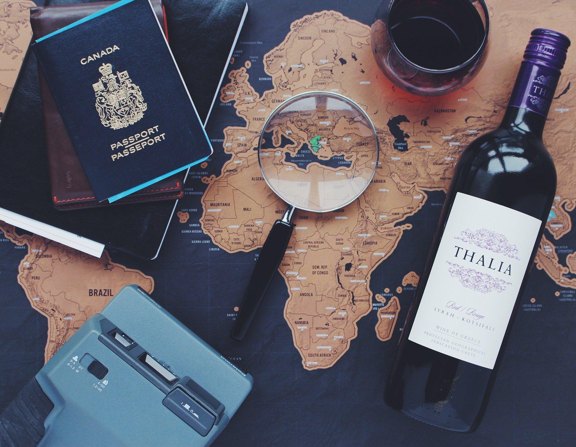 Imagem de um mapa mundo com uma lupa em cima, uma garrafa de vinho, passaportes e uma câmera. Imagem ilustrando texto franquia TZ Viagens