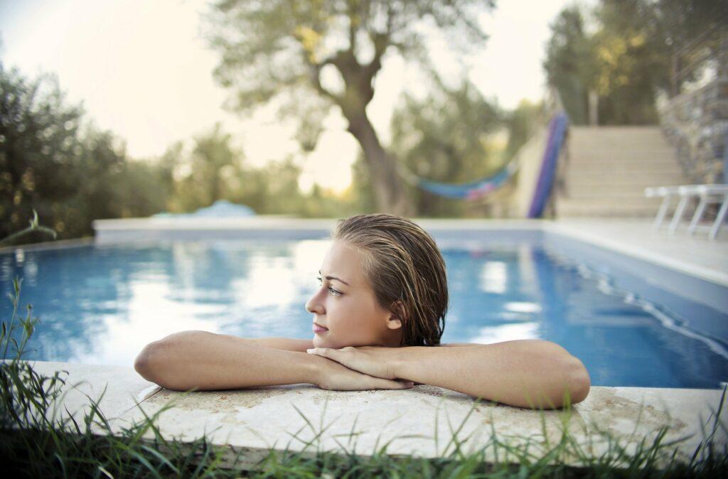 mulher na beira de uma piscina, vemos parte de uma grama, cadeira ao fundo, uma rede e árvores. Imagem ilustrativa para texto negócios com pouco investimento e retorno rápido.