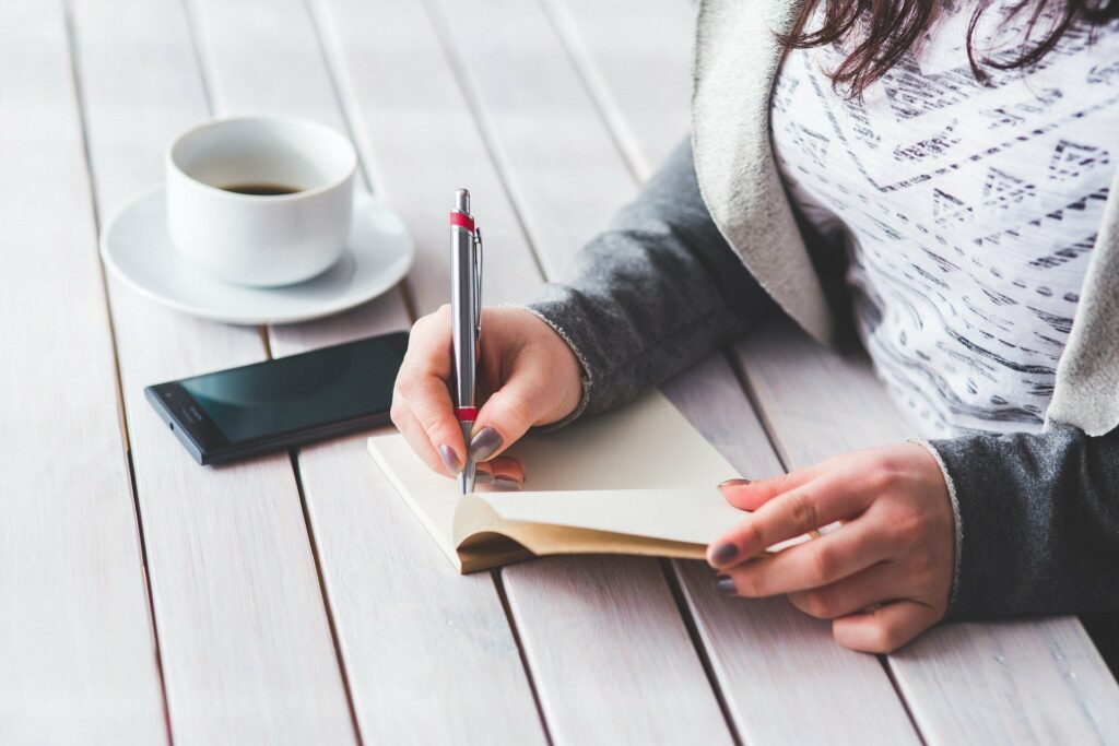 Foto de uma mulher com blusa estampada, fazendo anotações em um caderno, em cima de uma mesa branca de madeira. Ao lado temos uma xícara branca e celular. Imagem ilustrativa para texto negócios com pouco investimento e retorno rápido.