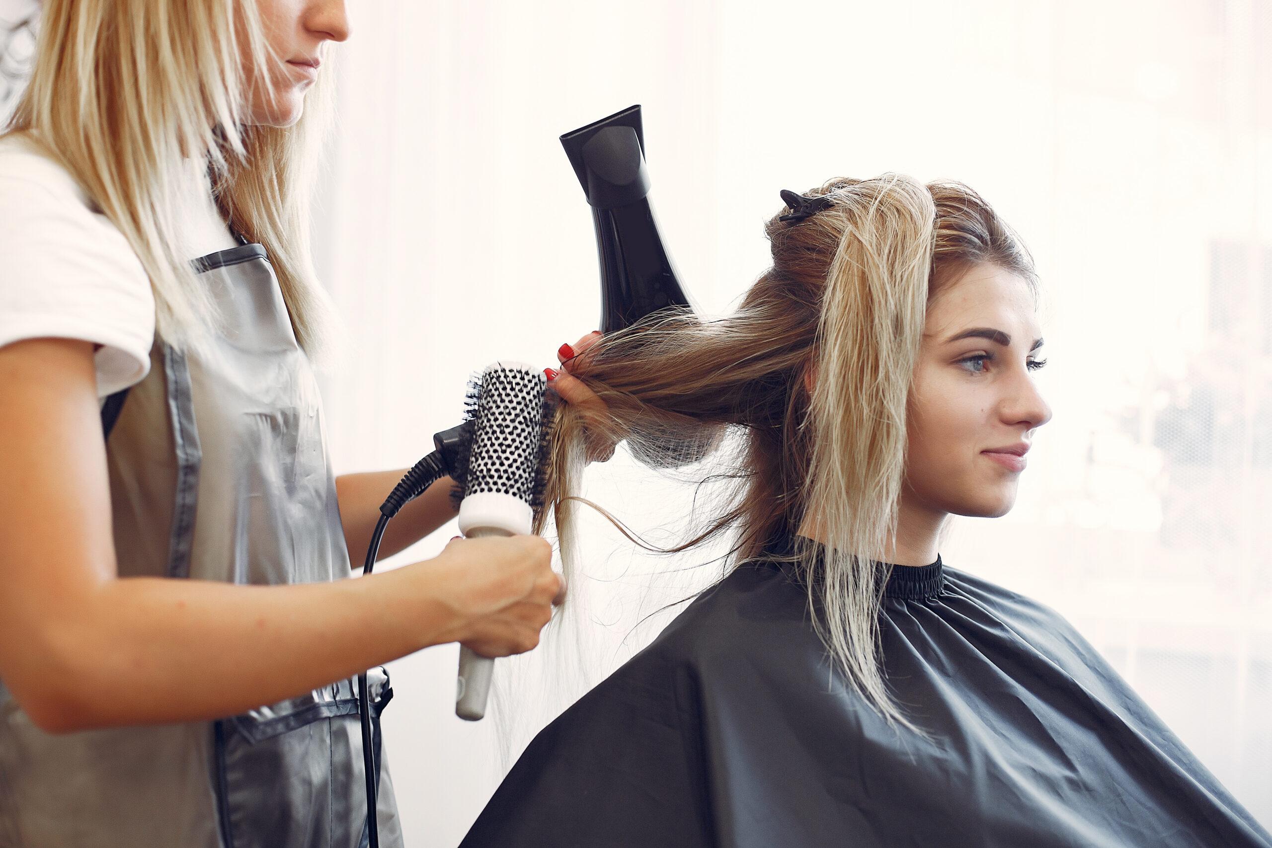 Mulher secando e fazendo escova no cabelo de outra mulher em um salão de beleza.