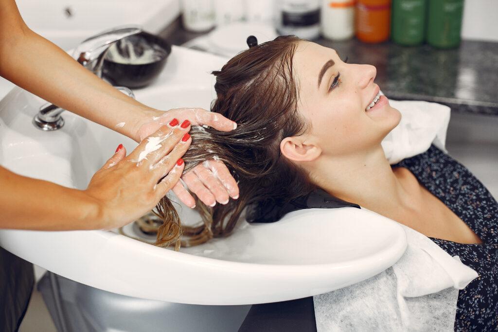 Mulher no salão de beleza lavando o cabelo. Imagem ilustrativa de texto como montar um salão de beleza em um espaço pequeno.