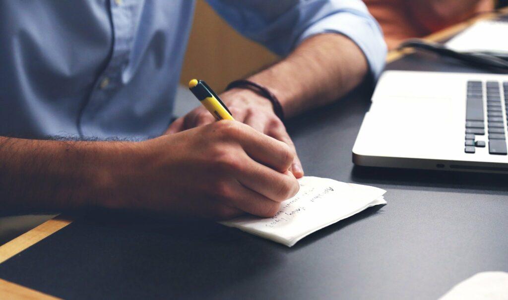 homem de blusa azul escrevendo em um papel ao lado vemos parte de um computador em uma mesa preta. Imagem ilustrativa para texto negócios com pouco investimento e retorno rápido.