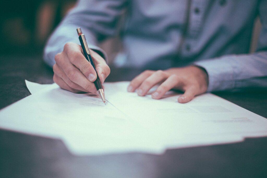 Pessoa de blusa azul assinando documentos em uma mesa preta. Imagem ilustrativa para texto montar um negócio.