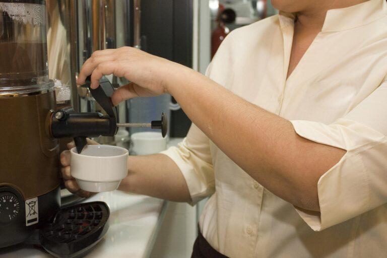 Mulher servindo um café em uma cafeteira.