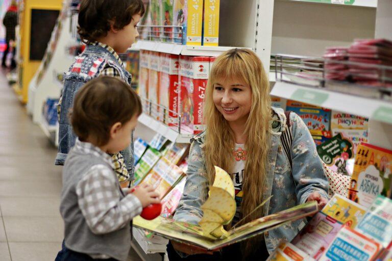 Imagem de uma mulher com duas crianças em uma loja de brinquedo escolhendo o briquedo.