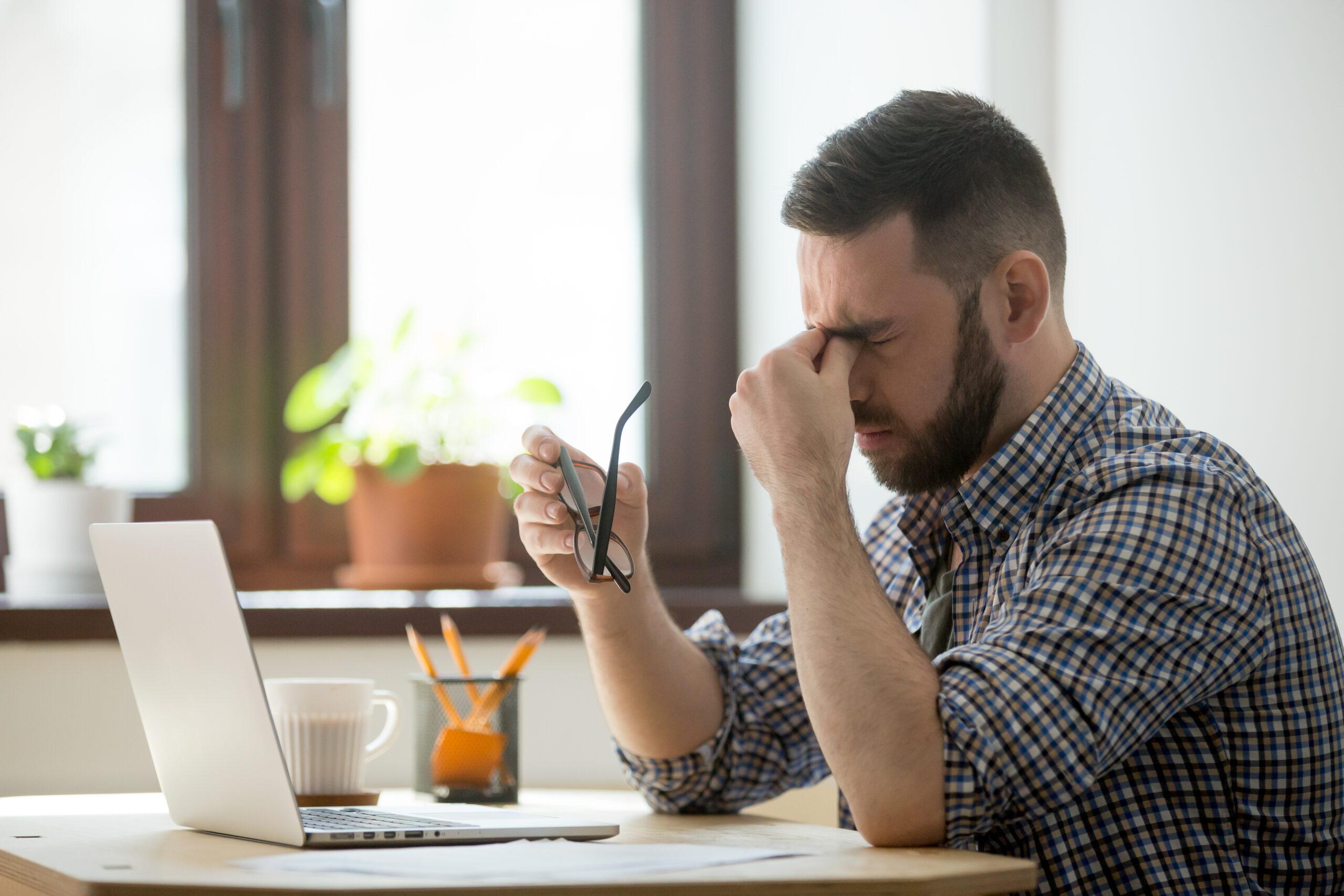 Imagem de um homem com cara de cansado em frente a um computador. Imagem ilustrativa de texto franqueados de sucesso