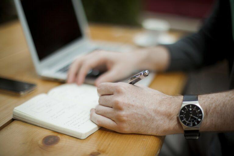 Pessoa escrevendo em um bloco de notas em uma mesa de escritório.