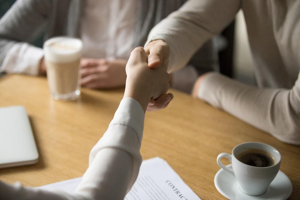 Foto de três pessoas ao redor de uma mesa de madeira, duas estão apertando as mãos. Vemos também copos com cafés e papéis. Imagem ilustrativa para texto encontre sua franquia.