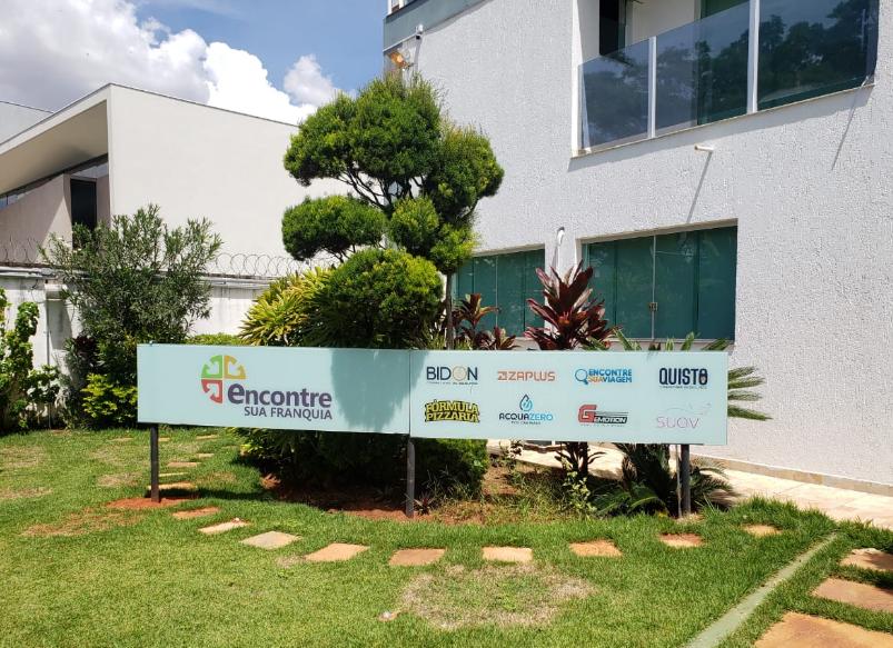 foto da placa da encontre sua franquia na sede da empresa, vemos um jardim ao lado de um prédio branco.
