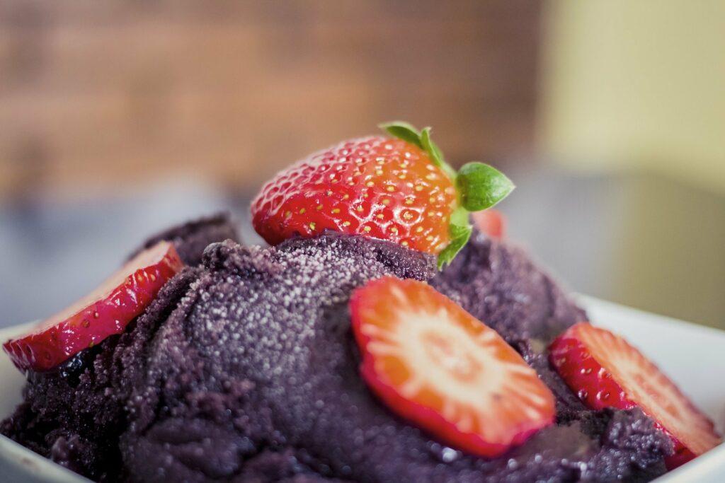Vemos na imagem, em foco, uma porção de creme de açaí com morangos e um fundo desfocado (imagem ilustrativa). Texto: franquia cream berry.