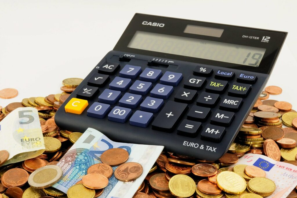 Vemos na imagem uma calculadora preta com várias moedas e notas ao redor.