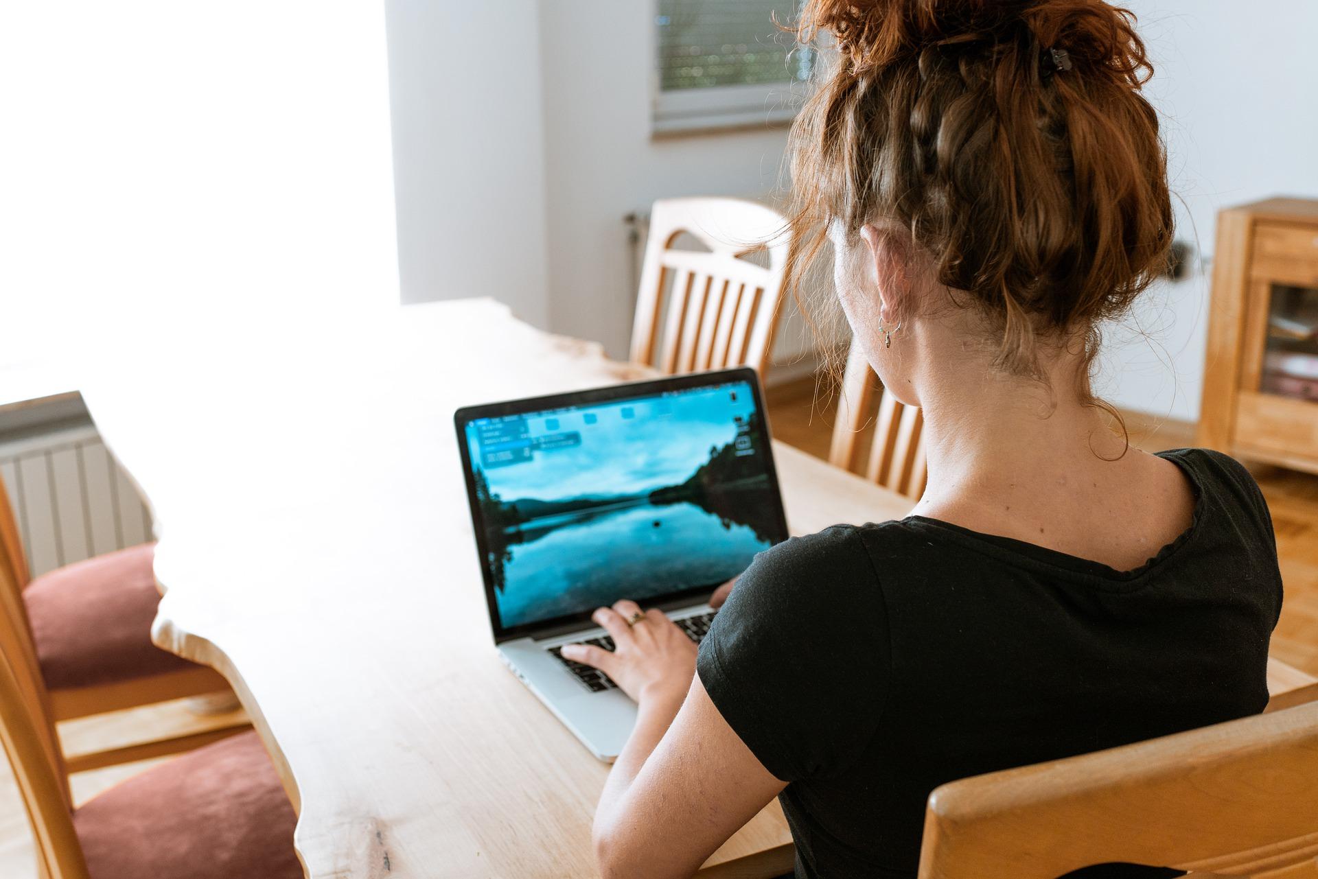 Vemos uma mulher trabalhando no computador em sua casa (imagem ilustrativa). Texto: franquias baratas de roupas.