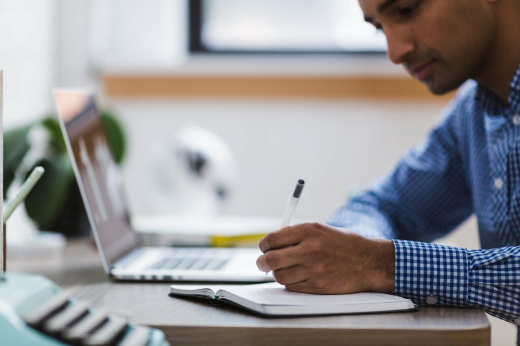 Homem de blusa azul escrevendo em um caderno com um computador do lado.