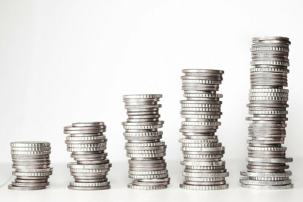 Vemos cinco pilhas de moedas pratas numa ordem crescente.