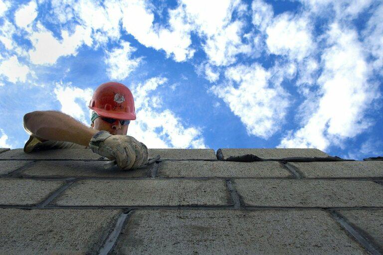pedreiro com capacete fazendo o acabamento em um muro com tijolos cinza, vemos o céu ao fundo. Imagem ilustrativa para texto franquias baratas construção 2021.