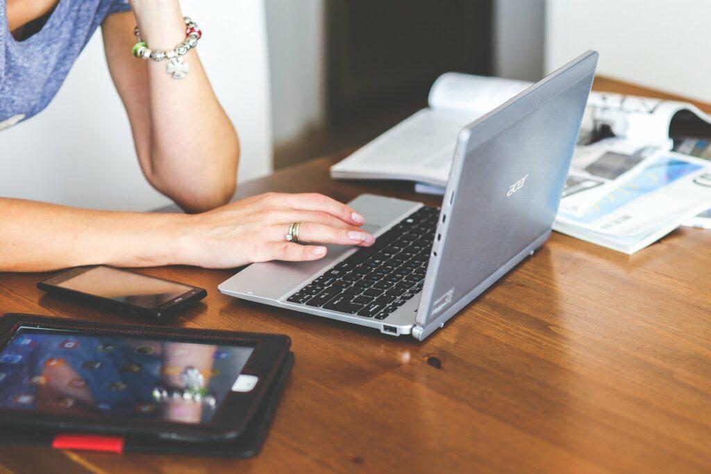 Vemos a foto de uma mulher utilizando um computador; sobre uma mesa de madeira temos livros, celular e um tablet.