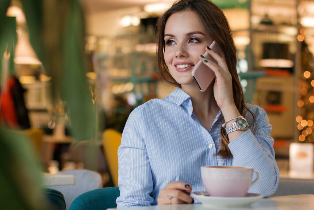 Vemos uma mulher de blusa azul segurando um celular rosa enquanto telefona; vemos ainda uma mesa branca e uma xícara.