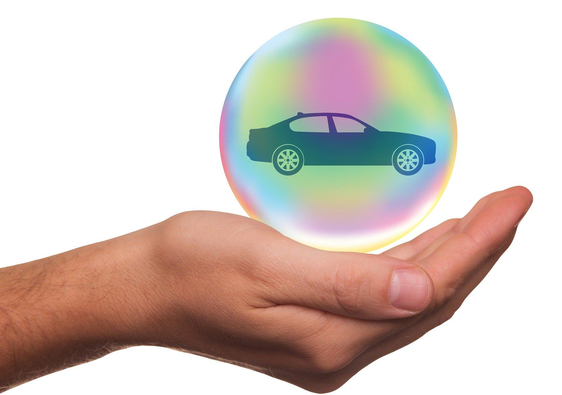 Vemos a mão de uma pessoa segurando uma bola de proteção colorida com um carro dentro.