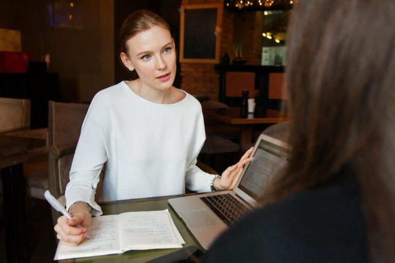 foto de uma mulher de blusa branca, atendendo uma pessoa enquanto segura um computador e um cadernos. Imagem ilustrativa para texto como abrir uma seguradora de veículos.