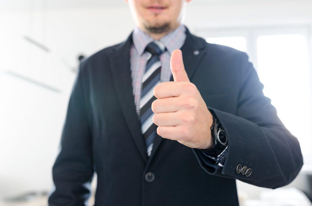 Vemos um homem de terno e gravada acenando positivamente com o seu polegar (imagem ilustrativa). Texto: escolher franquia.