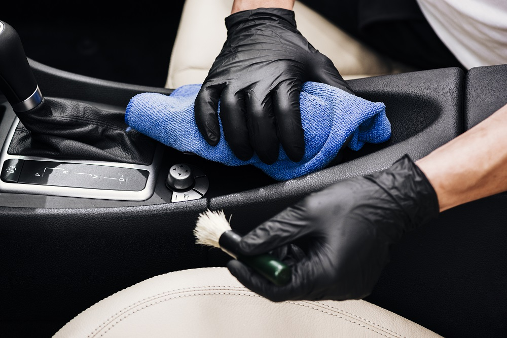 Vemos uma pessoa com luvas pretas usando pincel e uma toalha para fazer a limpeza interna do carro (imagem ilustrativa). Texto: franquia lavagem a seco.