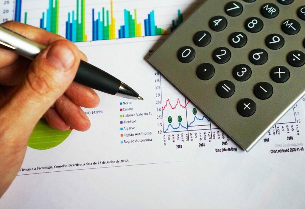 Imagem de uma calculadora em cima de folhas com gráficos e uma mão segurando uma caneta (imagem Ilustrativa). Texto: franquia de manicure express.