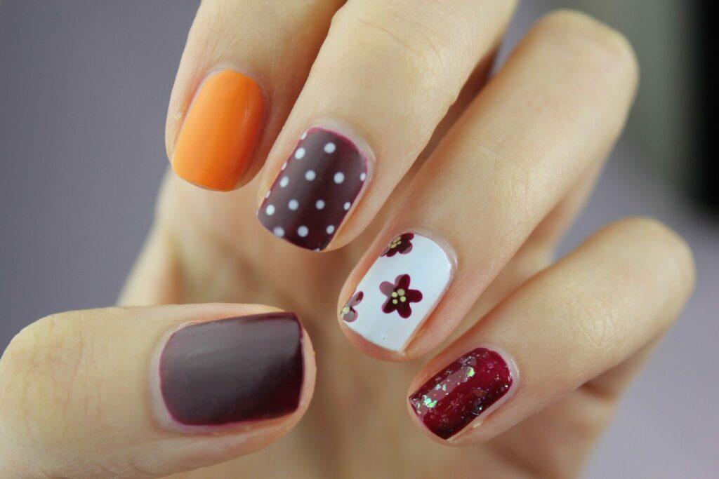 Imagem das unhas de uma mão todas pintadas e enfeitadas.