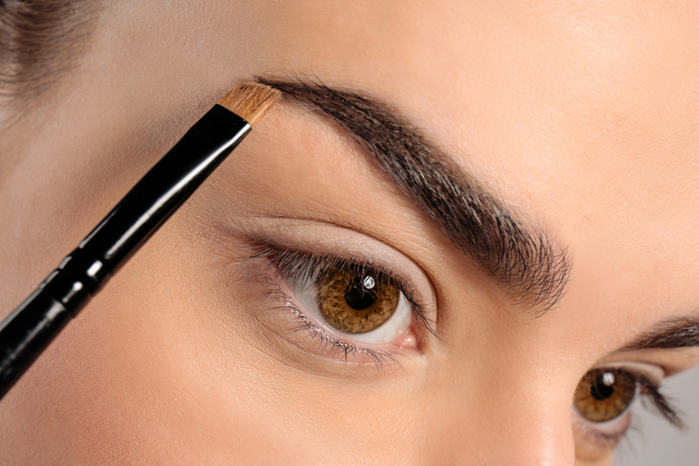 Imagem dos olhos de uma mulher e um pincel sendo aplicado na sobrancelha. Imagem ilustrativa texto franquia de manicure express.