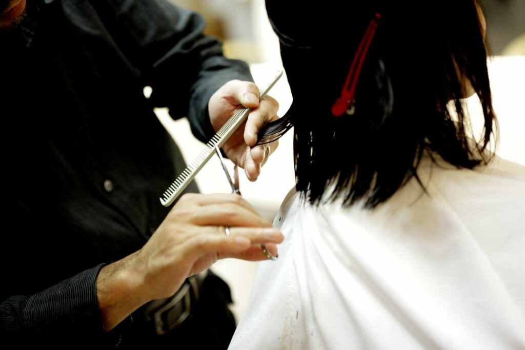 Pessoa cortando o cabelo de outra pessoa.