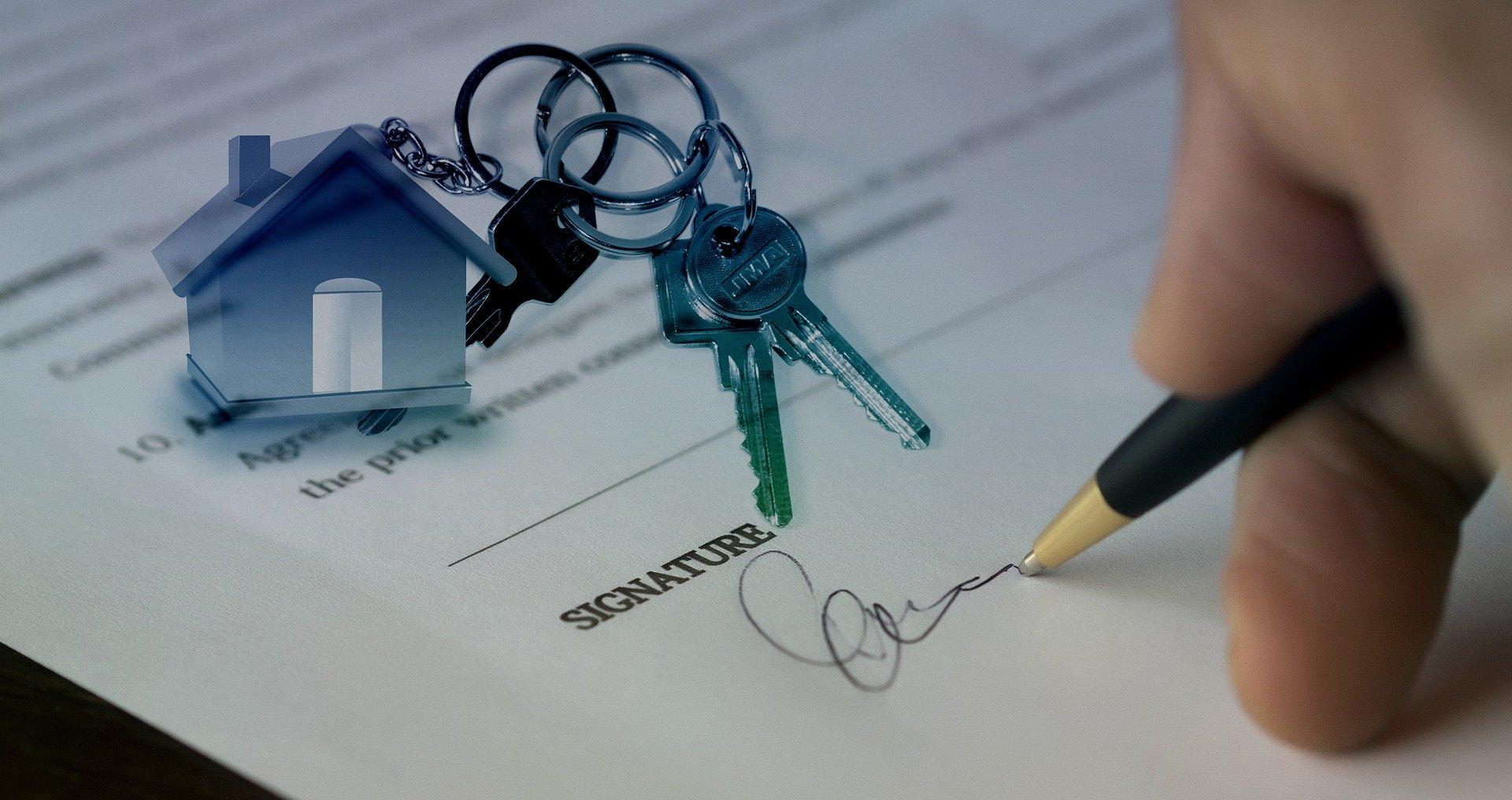 Imagem de uma mão assinando um contrato com um desenho de chaves e de uma pequena casa.