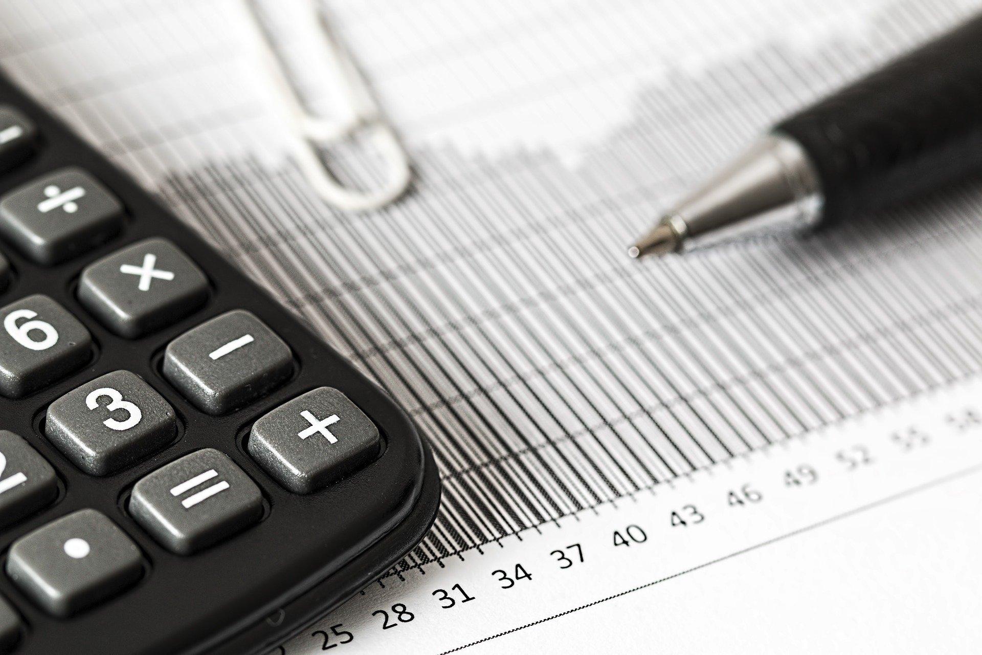 Vemos uma calculadora e uma caneta sobre uma imagem de um gráfico (imagem ilustrativa). Texto: franquia de negócios e serviços.