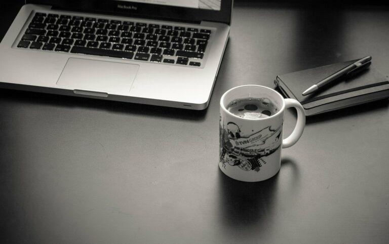 foto de uma mesa preta com computador, caderno e uma xícara ao lado. Imagem ilustrativa para texto franquia home office 2021.