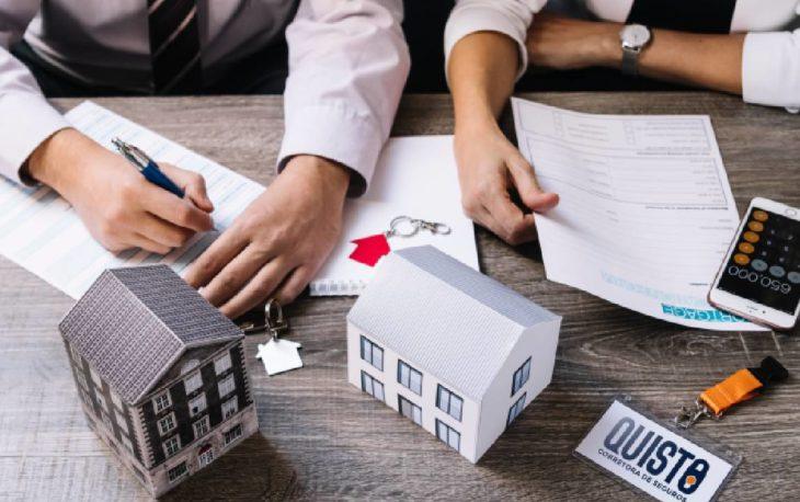 Vemos duas miniaturas de casas em cima de uma mesa de escritório (imagem ilustrativa). Texto: negócios lucrativos com pouco dinheiro.