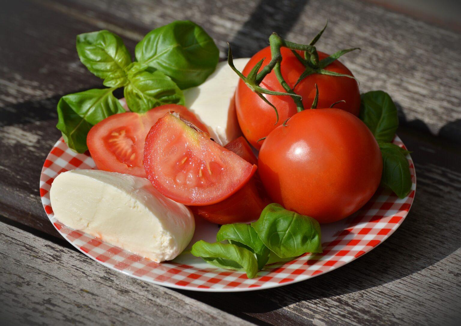 Imagem de uma salada Caprese, com tomates, folhas verdes e um pedaço de queijo.