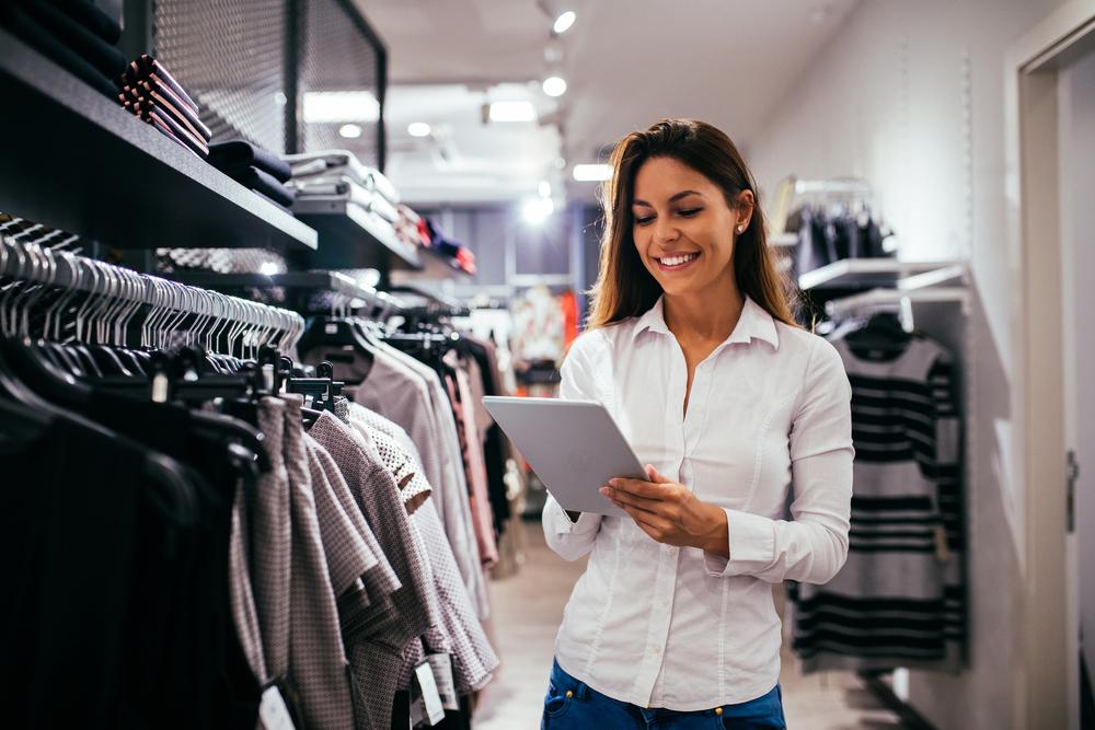 Vemos uma mulher em uma loja de roupas segurando um tablet ao lado de várias pecas penduradas em cabides (imagem ilustrativa).