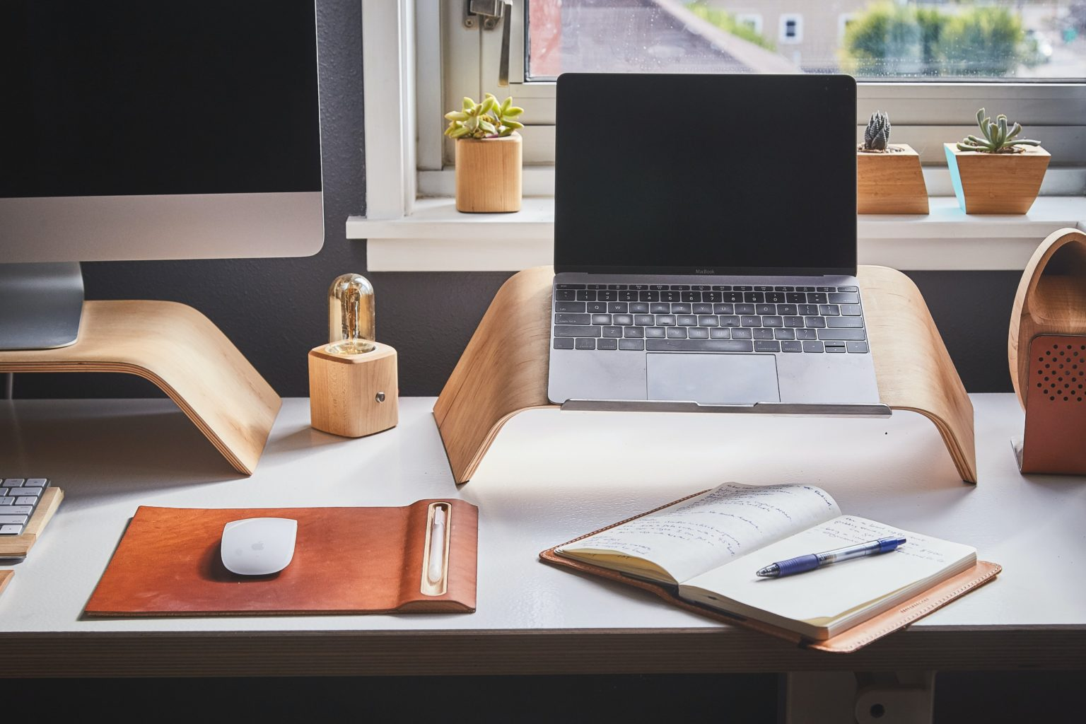 Vemos uma mesa de trabalho em casa com computador e uma caderneta de anotações (imagem ilustrativa). Texto: franquias baratas home office.