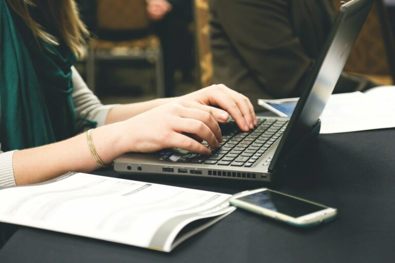 foto de uma mulher usando um computador com caderno e celular ao lado. imagem ilustrativa para texto franquias boas para abrir.