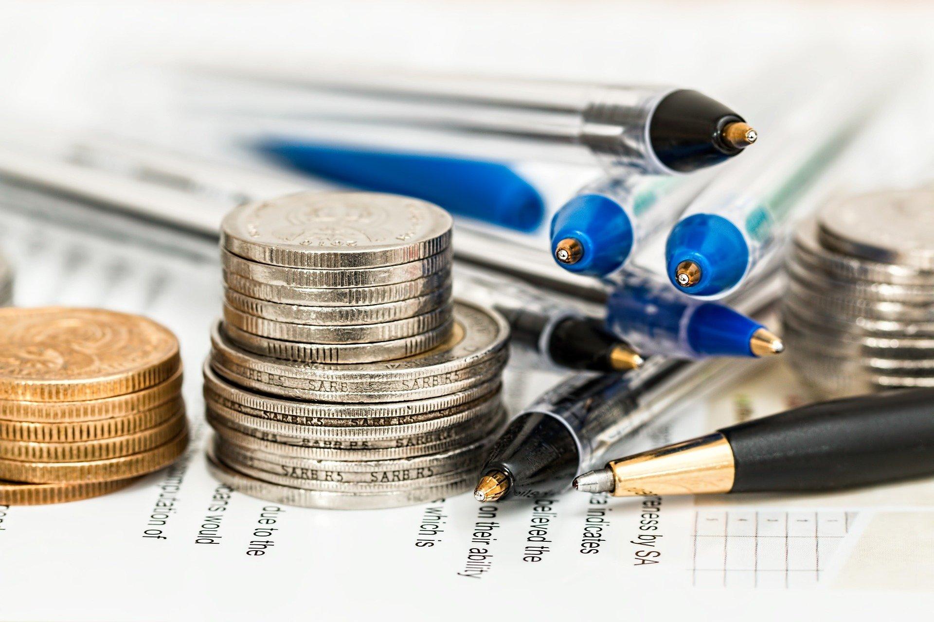 Imagem de canetas e algumas moedas empilhadas. Imagem ilustrativa texto franquias com menos de 50 mil.