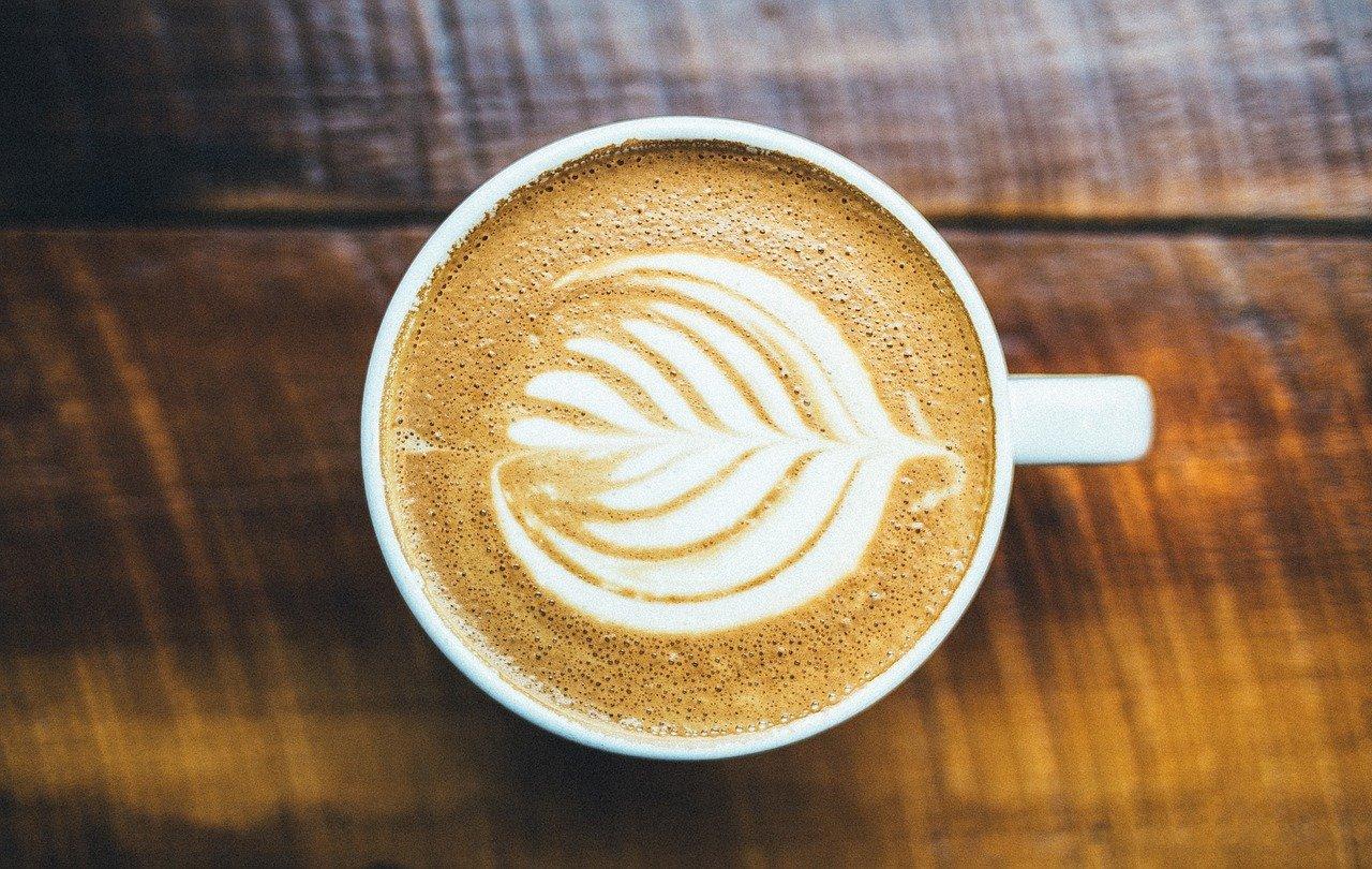 Vemos um xícara café com leite decorando com o formato de uma folha de árvore (imagem ilustrativa).