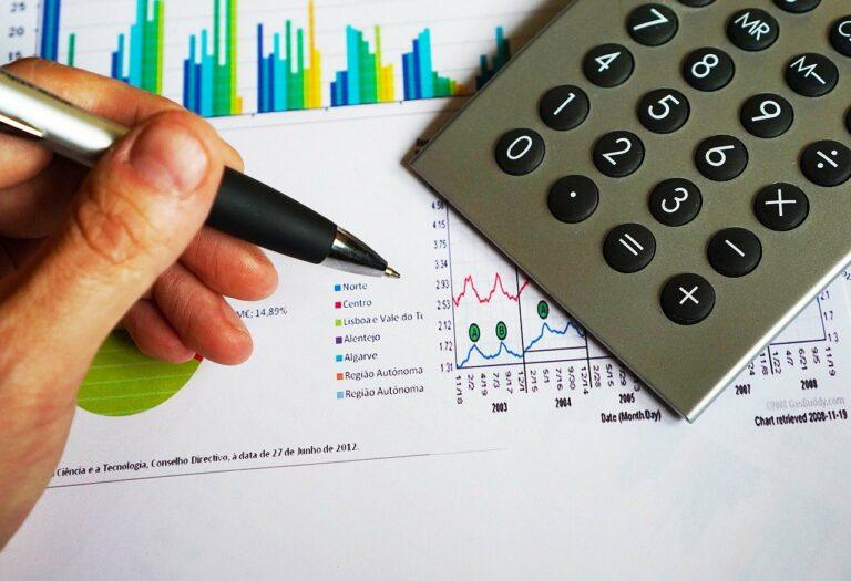 Imagem de uma mão segurando uma caneta e uma calculadora ao lado sobre uma folha com gráficos. Imagem ilustrativa texto franquias de 50 mil.