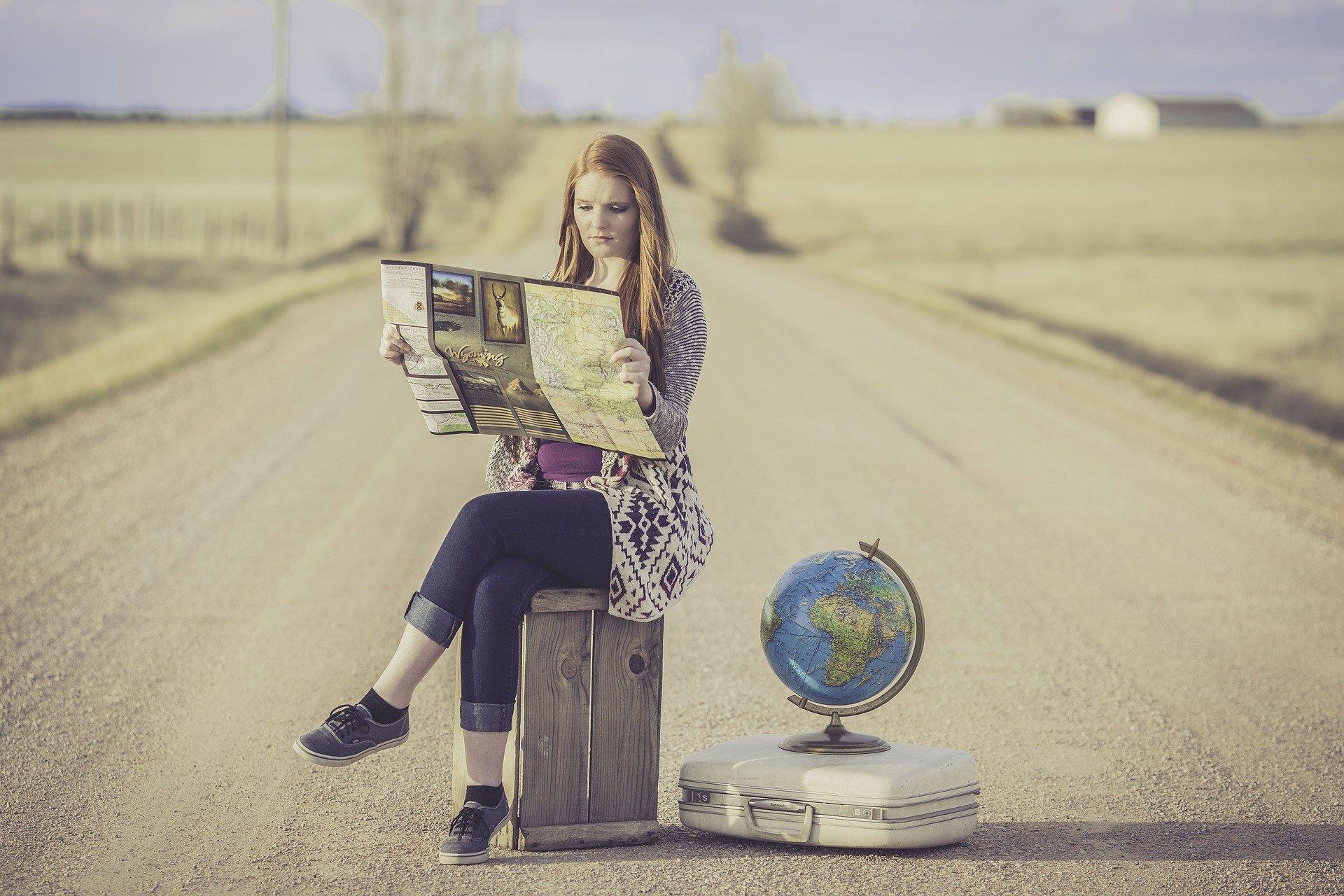 Imagem de uma mulher sentada em um banco no meio de uma estrada (imagem ilustrativa).