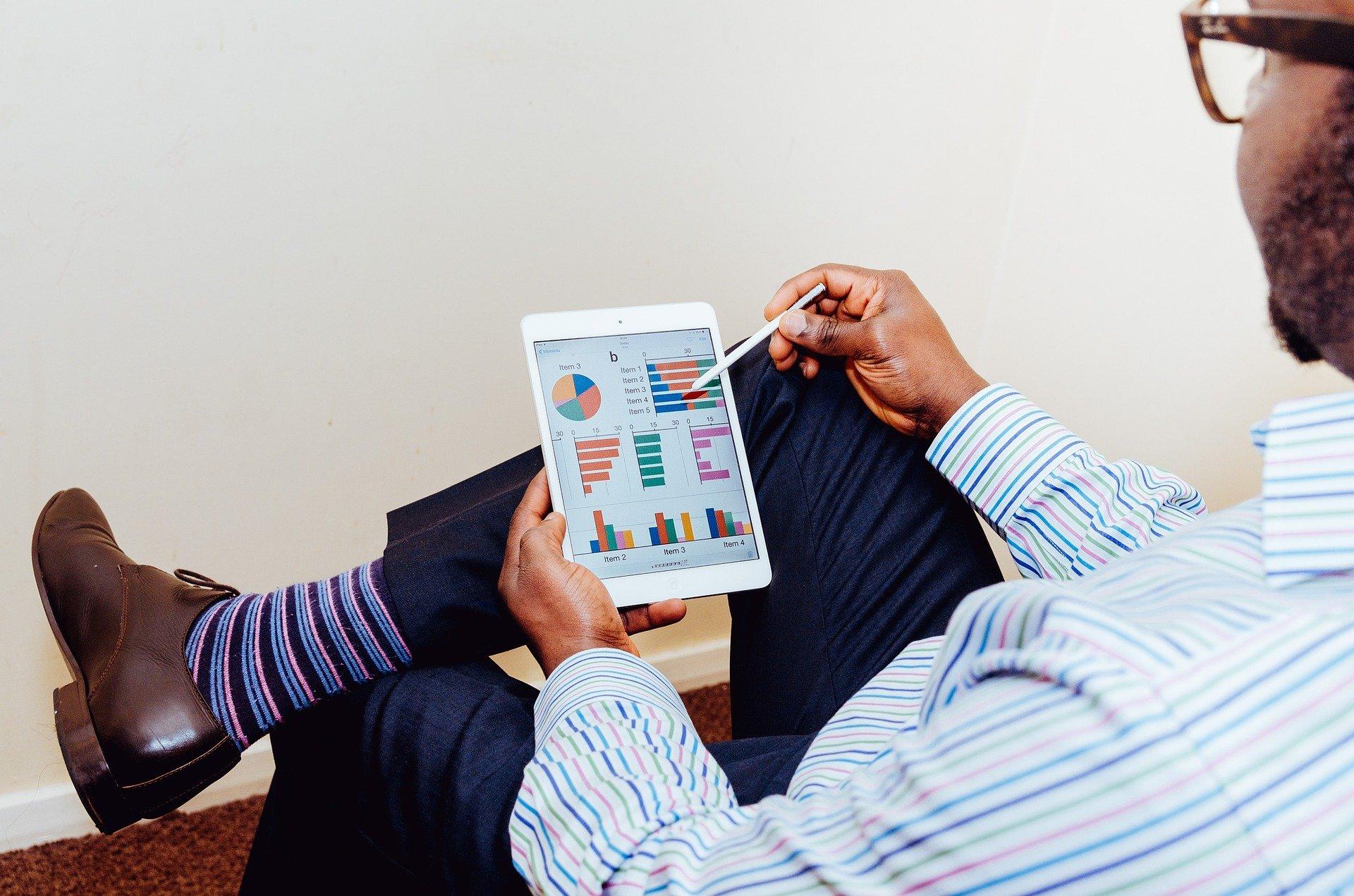 Um homem segura um tablet com alguns gráficos em tela; atendo, enquanto segura uma caneta, ele os analisa (imagem ilustrativa). Texto: melhor negócio para se investir.