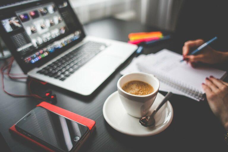 Foto de uma mesa preta com computador, xícara de café e celular, enquanto uma pessoa faz anotações em um caderno. Imagem ilustrativa para texto melhores franquias 2021.