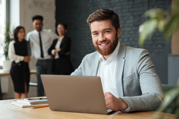 Vemos um empresário sorrindo (imagem ilustrativa). Texto: comprar franquia.